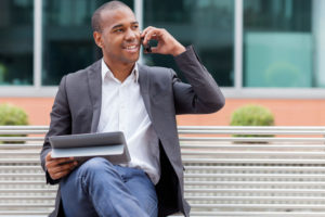 Smiling afro american manager sitting on a bench and phoning